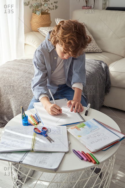 High angle of boy with curly hair sitting on sofa near round table and writing in notebook while doing homework in cozy living room at home