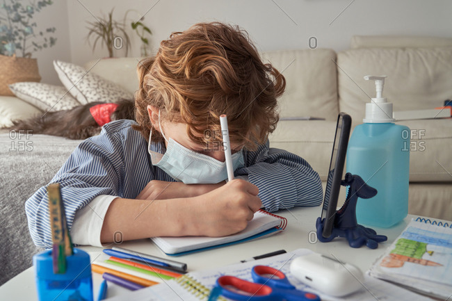Boy in medical mask making notes in notepad while sitting at table with smartphone and disinfectant and studying online during quarantine