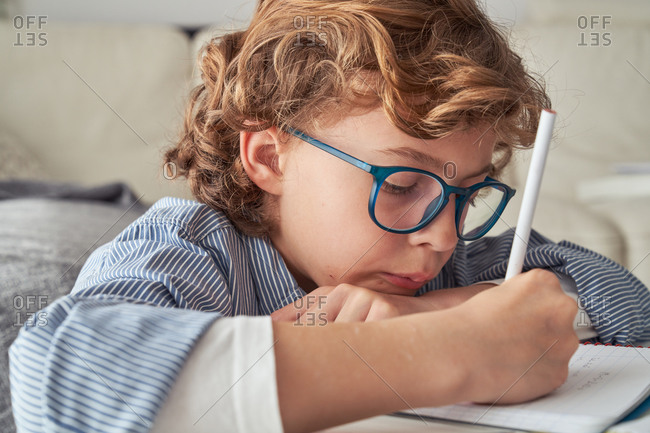 Boy with curly hair sitting on sofa near round table and writing in notebook while doing homework in cozy living room at home