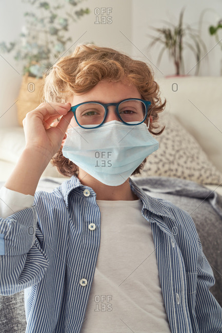 Smart boy in medical mask putting on glasses while sitting near table with notebook and preparing for remote studies at home