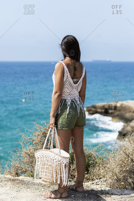 Rear view of an attractive hispanic woman holding a handbag while standing on seashore looking to horizon