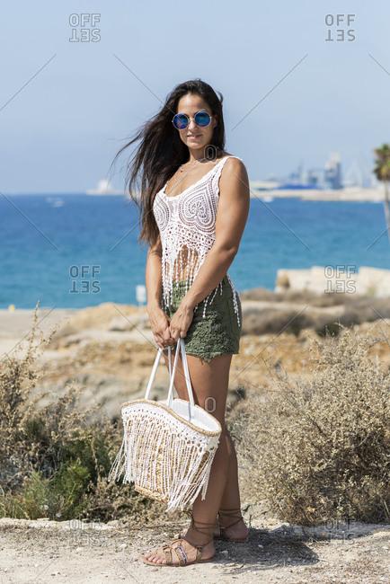 Pretty hispanic woman standing at seaside holding a handbag and looking camera