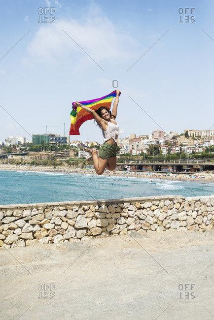Brunette girl with gay pride flag on a windy sea view beach