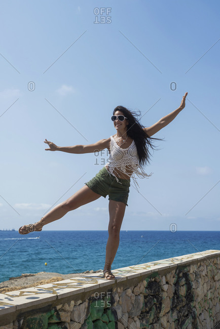 Full-length portrait of carefree brunette woman in shorts dancing on a wall against sea