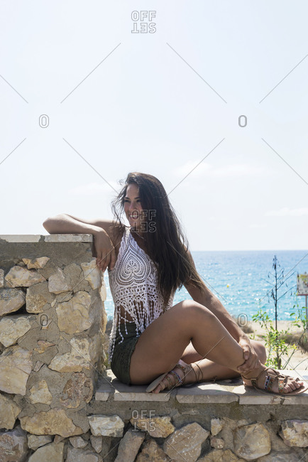 Intimate portrait of young woman posing at the sea.