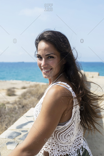 Pretty long haired woman standing on seaside while looking camera with a beautiful smile