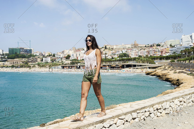 Young hispanic woman with sunglasses walking seaside against a tourist town in Spain
