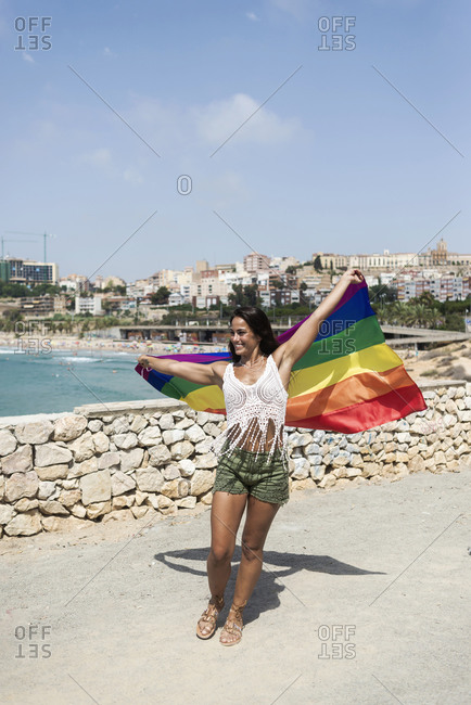 Portrait of a pretty hispanic woman playing with a lgtb flag