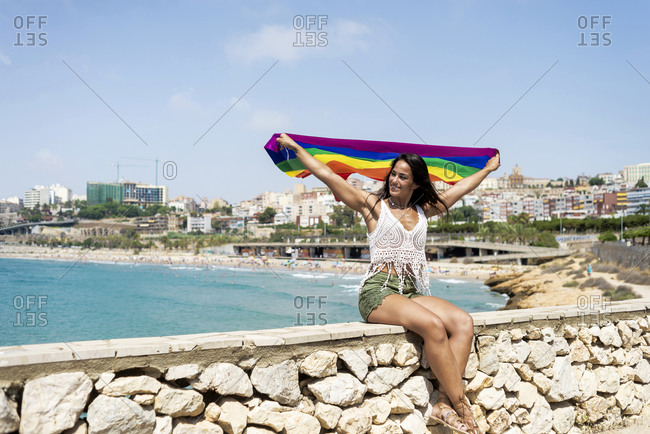 Portrait of a pretty hispanic woman holding a lgtbi flag