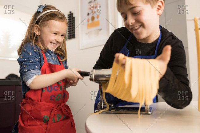 A little girl with older brother using pasta machine while preparing homemade noodles in home kitchen