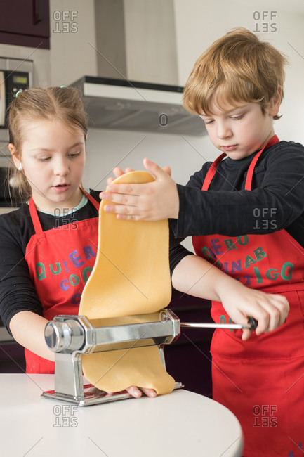 A little girl with her brother using pasta machine while preparing homemade noodles in home kitchen
