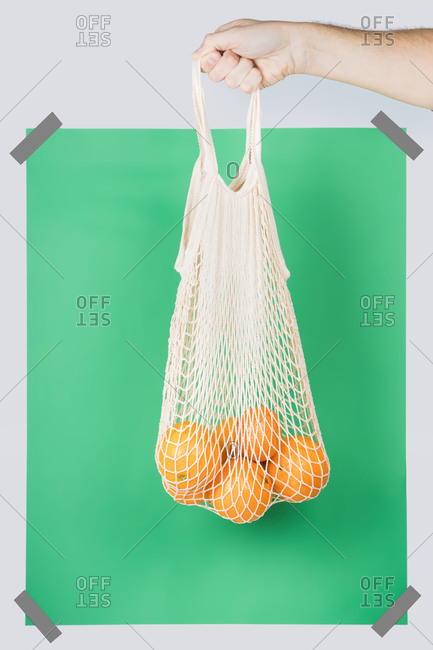 Unrecognizable person carrying net bag with ripe oranges against green rectangle during zero waste shopping