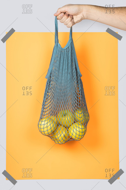Unrecognizable person hand carrying net bag with ripe apples against orange rectangle during zero waste shopping