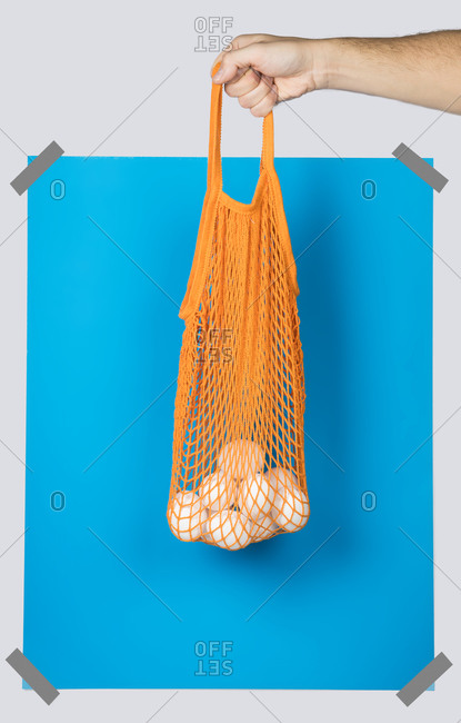 Unrecognizable person carrying orange net sack with fresh eggs against blue rectangle during zero waste shopping