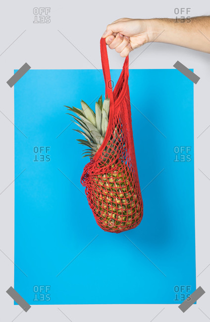 Unrecognizable person carrying net bag with ripe pineapple against blue rectangle during zero waste shopping