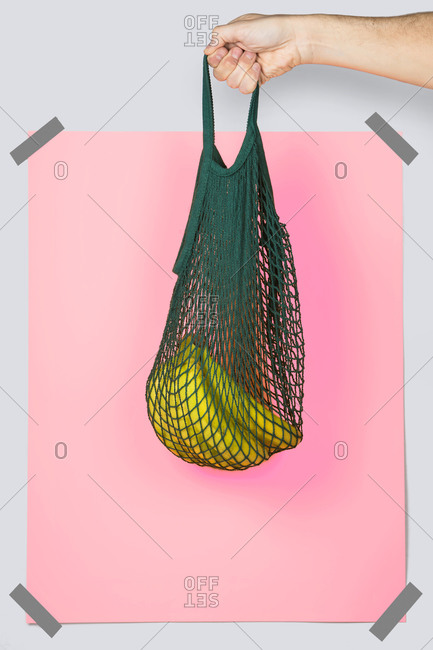 Unrecognizable person carrying net bag with ripe bananas against pink rectangle during zero waste shopping