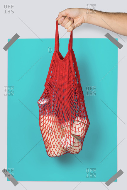 Anonymous person carrying red string sack with glass containers of dairy against turquoise rectangle during eco friendly shopping