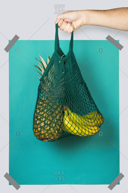 Unrecognizable person carrying net bag with ripe pineapple and bananas against blue turquoise rectangle during zero waste shopping