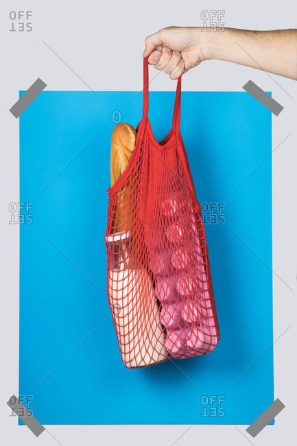 Unrecognizable person carrying net bag with various groceries against blue rectangle during zero waste shopping