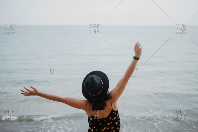 High angle back view of female in black hat and dress standing with arms raised and enjoying life on beach against troubled ocean waves in overcast weather
