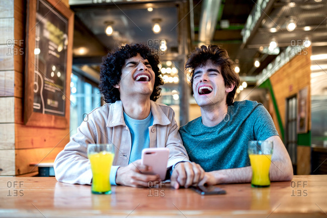 Multiethnic young homosexual men browsing social media on smartphone and having fresh drinks smiling with closed eyes while sitting at cafe table during romantic date