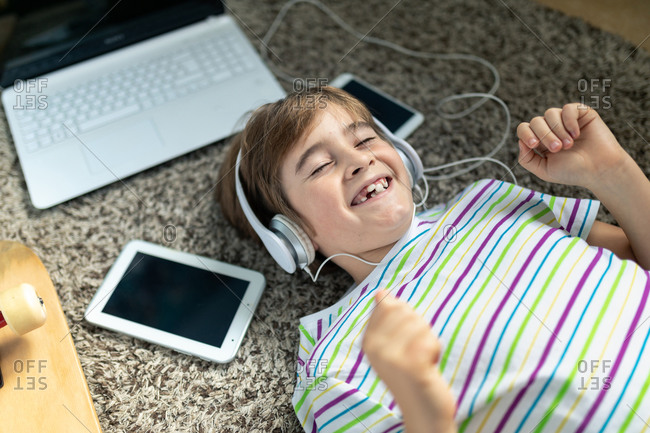 From above of cheerful little boy in casual shirt listening to music with headphones while lying on carpet near gadgets and skateboard in bedroom