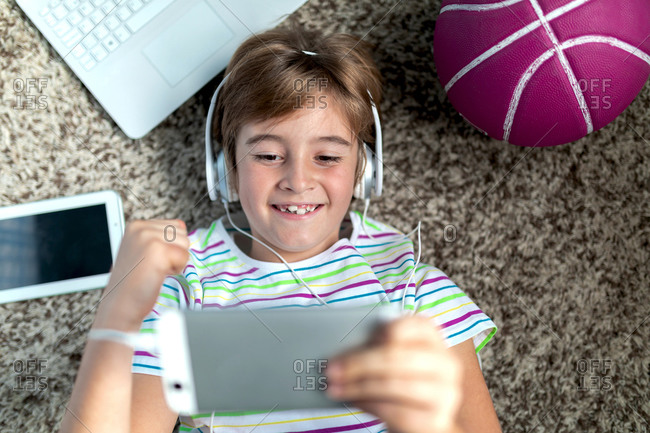 From above of cheerful little boy in headphones lying on floor near gadgets and ball and playing video game on tablet while spending time at home