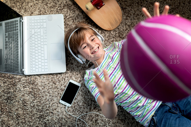 From above of cheerful boy in casual wear listening to music with headphones and smartphone and tossing ball while lying on carpet in room
