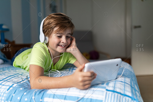 Positive preteen boy in casual wear with headphones lying on bed and watching movie on tablet while resting at home