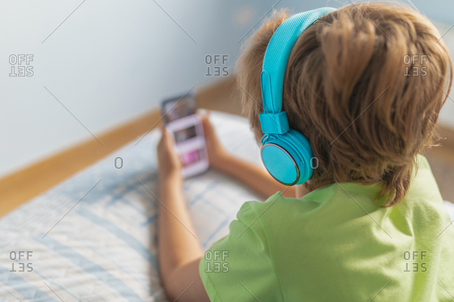 Back view boy in casual wear with headphones lying on bed and watching movie on tablet while resting at home