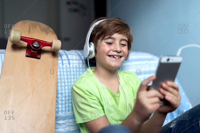 Laughing little boy with headphones listening to music and chatting with friends in social network while sitting near skateboard in bedroom