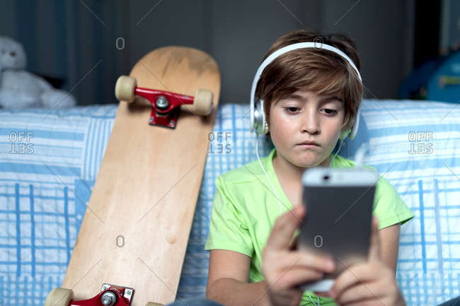 little boy with headphones listening to music and chatting with friends in social network while sitting near skateboard in bedroom