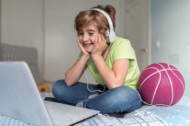 Cheerful schoolboy in casual outfit and headphones screaming loudly while celebrating victory in video game on laptop at home