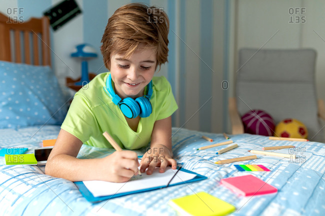 Side view of positive schoolboy in casual wear and wireless headphones enjoying music and drawing with pencils while spending free time in bedroom