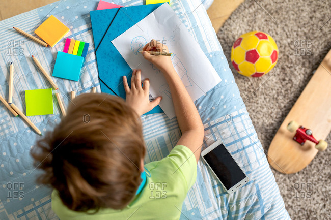 From above of cheerful little kid in casual shirt looking at camera and smiling while listening to music with headphones and drawing with colorful pencils on bed