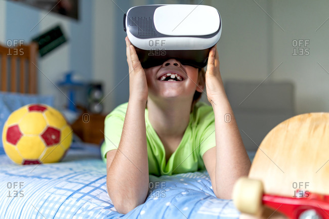 Cheerful little boy in VR goggles enjoying virtual reality while lying on bed near ball and skateboard during weekend at home