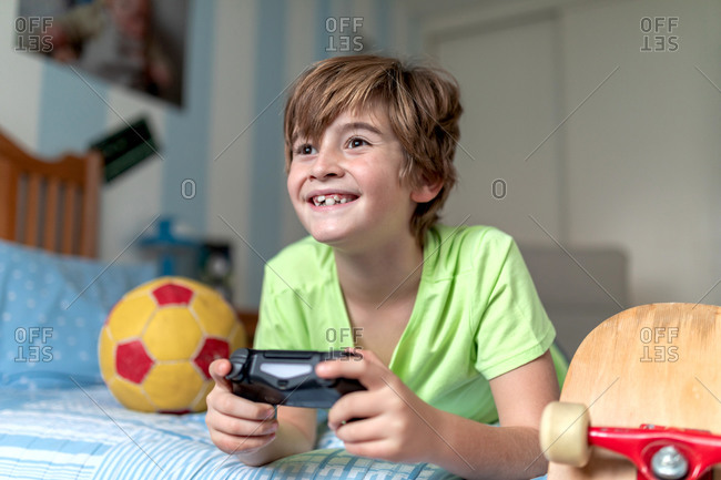 Cheerful little boy spending time at home and playing video game while lying on bed with ball and skateboard placed nearby