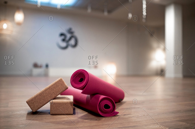 Yoga blocks and rolled pink mats placed on floor in spacious brightly illuminated studio