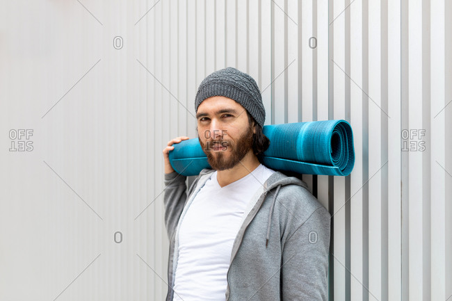 Bearded guy looking at camera with rolled mat supporting neck while leaning on wall during yoga training