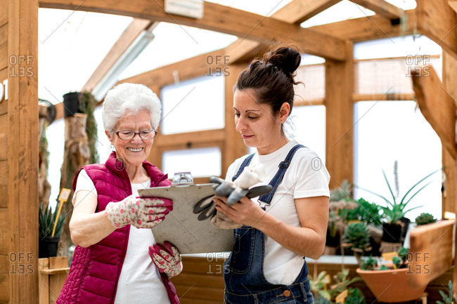 Adult woman writing on clipboard near elderly colleague while working in hothouse together