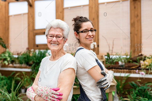 Side view of positive elderly and adult women in gloves and glasses smiling for camera and crossing arms while working in indoor garden together