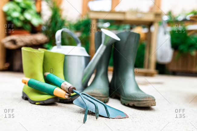 Gardening tools placed on floor near rubber boots and watering can in greenhouse