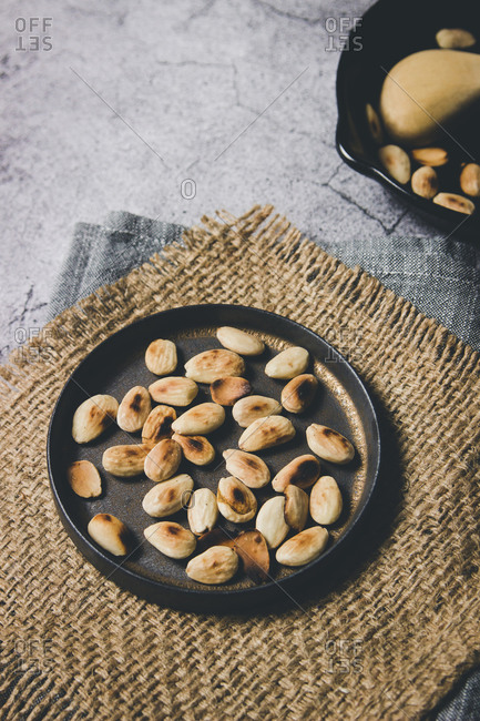 From above tasty roasted almond nuts on black metal pan on burlap napkin in composition with wooden spoon on gray rustic table