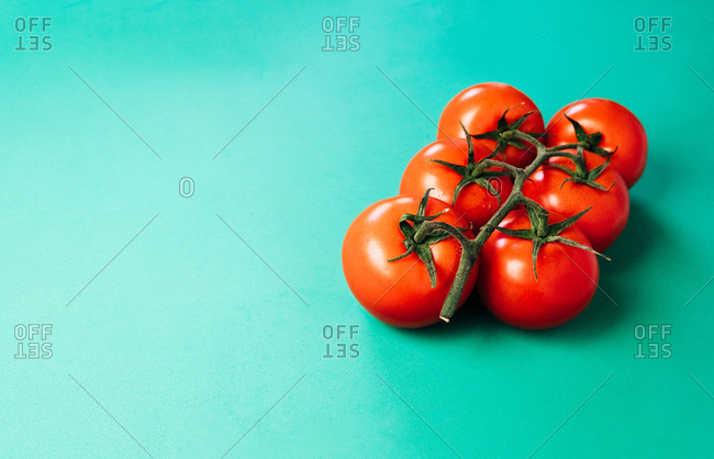 From above bunch of healthy red tomatoes placed on bright turquoise background