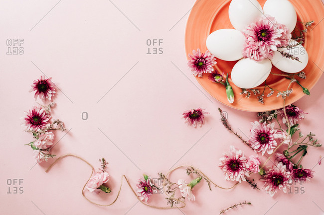 Top view of bunch of delicate flowers arranged near plate with chicken eggs on Easter Day on pink background