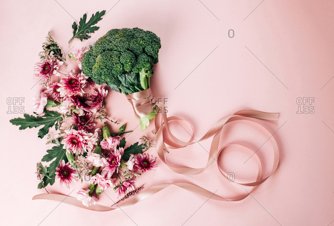 Top view of bunch of pretty flowers and ripe broccoli with silk ribbon arranged on pink background on summer day