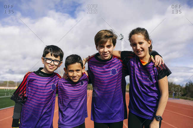 Friends in a sports team standing on running track- with arms around