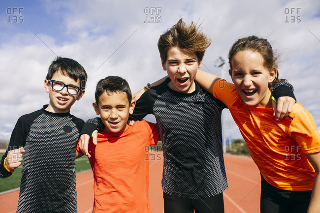 Friends in a sports team standing on running track- with arms around- shouting