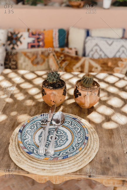 Morocco- Table with two potted cacti and cutlery lying on ornate plate