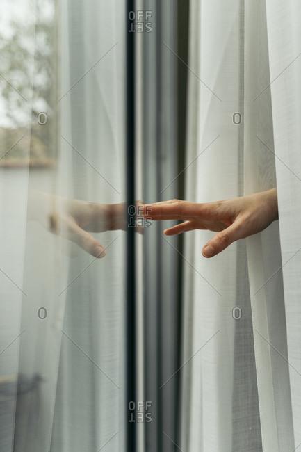 Hand of a woman touching windowpane